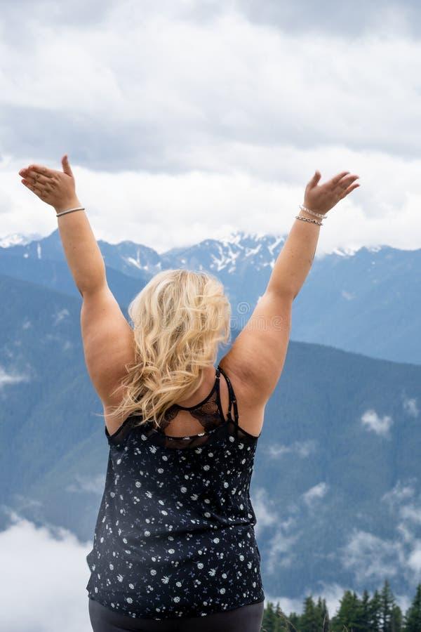 A mulher loura com a parte traseira que enfrenta a câmera tem os braços aumentados no furacão Ridge no parque nacional olímpico imagem de stock royalty free