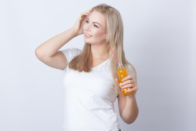 Mulher loura com soda alaranjada em suas mãos foto de stock
