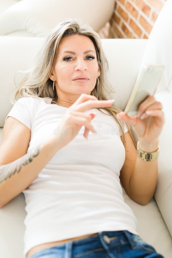 Mulher loura com tatuagem nas calças de brim usando o telefone esperto que encontra-se no sofá branco fotos de stock