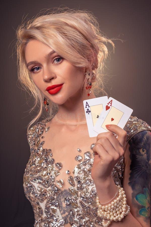 A mulher loura com um penteado bonito e uma composição perfeita está levantando com os cartões de jogo em suas mãos Casino, p?que foto de stock