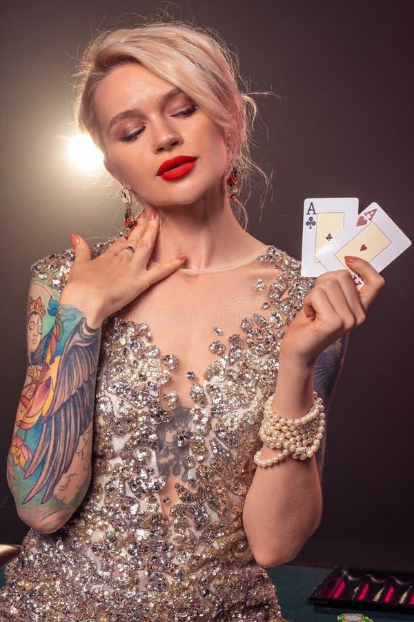 A mulher loura com um penteado bonito e uma composição perfeita está levantando com os cartões de jogo em suas mãos Casino, p?que fotos de stock royalty free