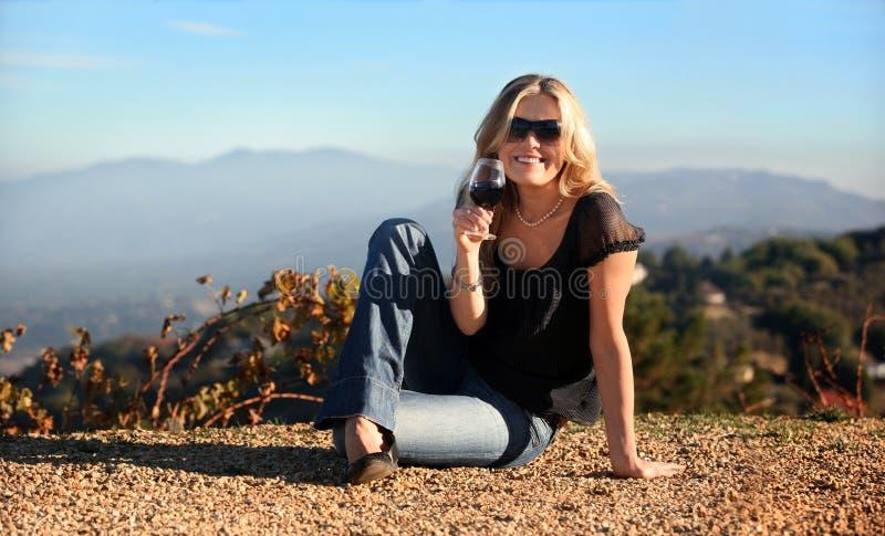 Mulher loura com um vidro do vinho foto de stock