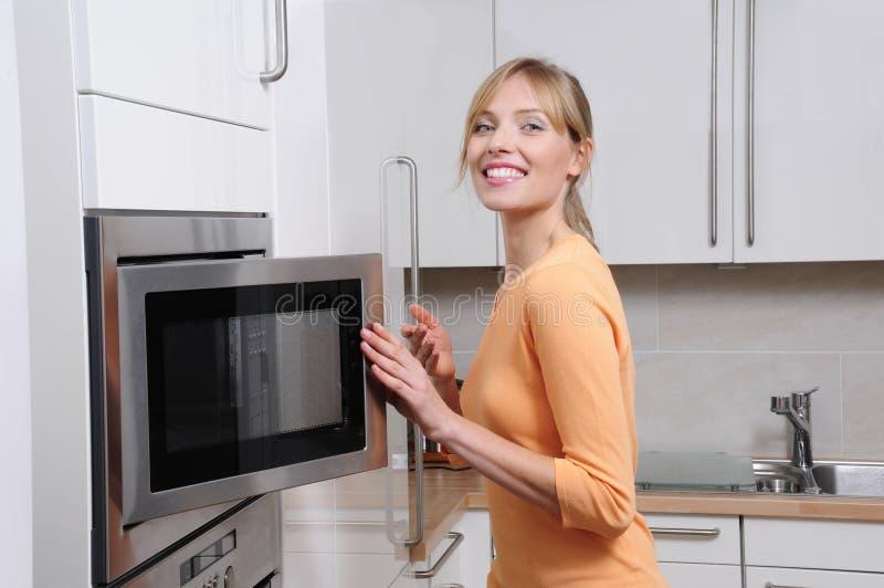 Mulher loura com uma microonda fotografia de stock