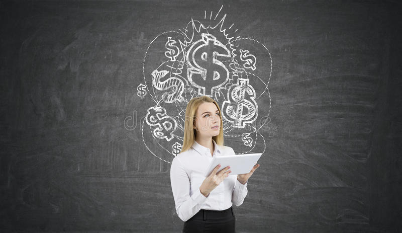 Mulher loura com uma tabuleta perto do quadro com sinais de dólar fotos de stock