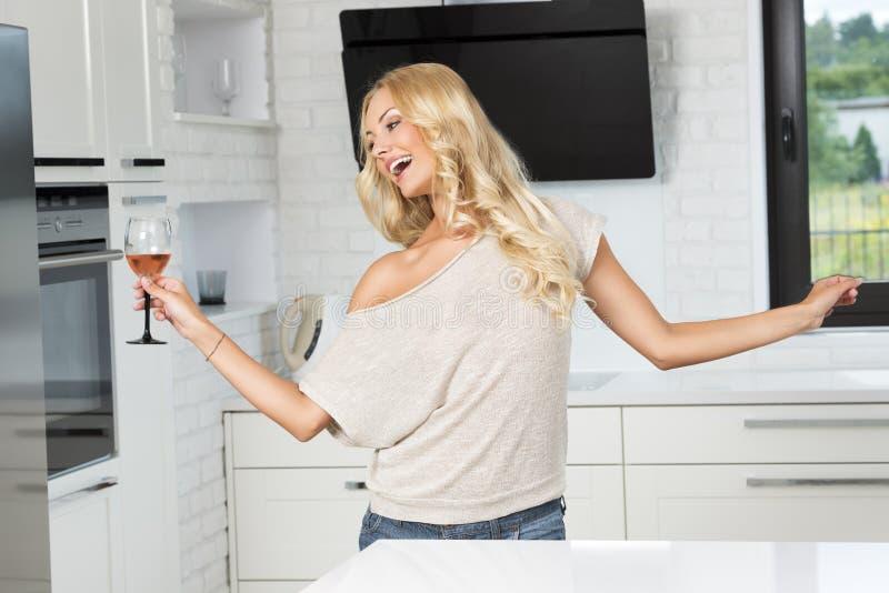 Mulher loura completamente da alegria com vidro do vinho imagens de stock
