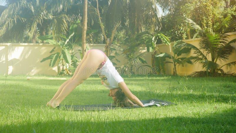 Mulher loura consideravelmente nova na camisa branca na grama verde no dia ensolarado que faz a ioga fotografia de stock royalty free