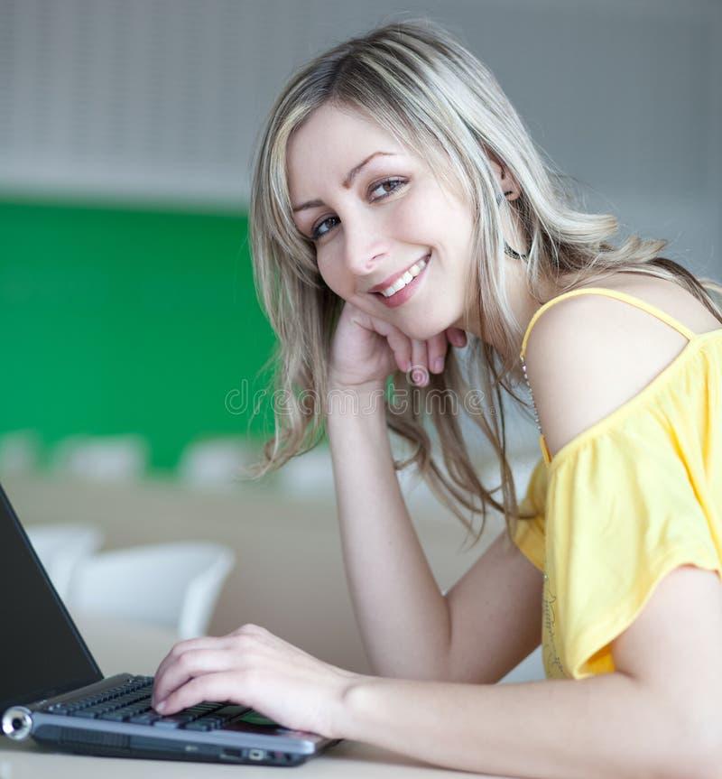 Mulher loura consideravelmente nova que trabalha em um portátil foto de stock royalty free