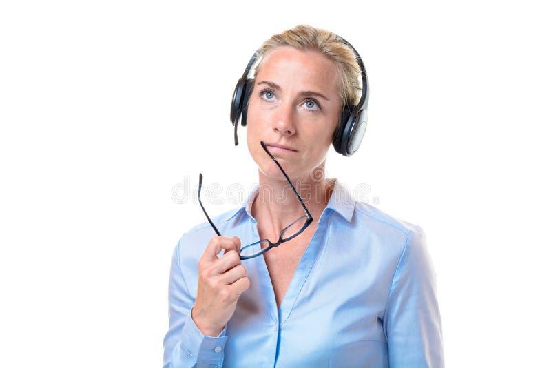 Mulher loura curiosa com auriculares do telefone foto de stock royalty free