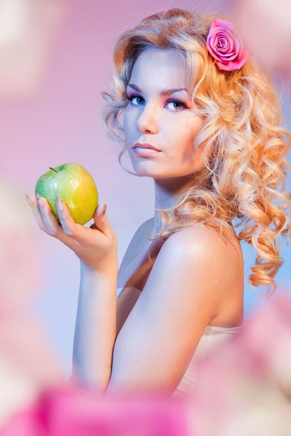 Mulher loura Curly com maçã verde foto de stock