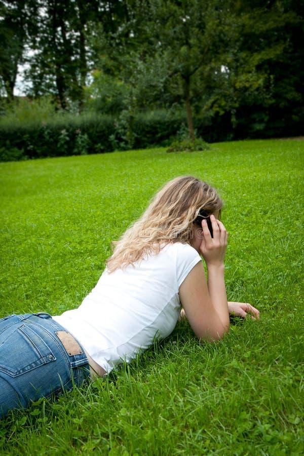 Mulher loura curly nova que telefona em um parque foto de stock