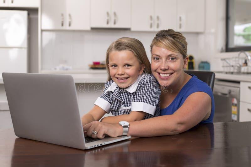 Mulher loura da mãe junto com sua menina bonita e doce nova 6 a 8 anos velha sentando em casa a cozinha que aprecia com foto de stock