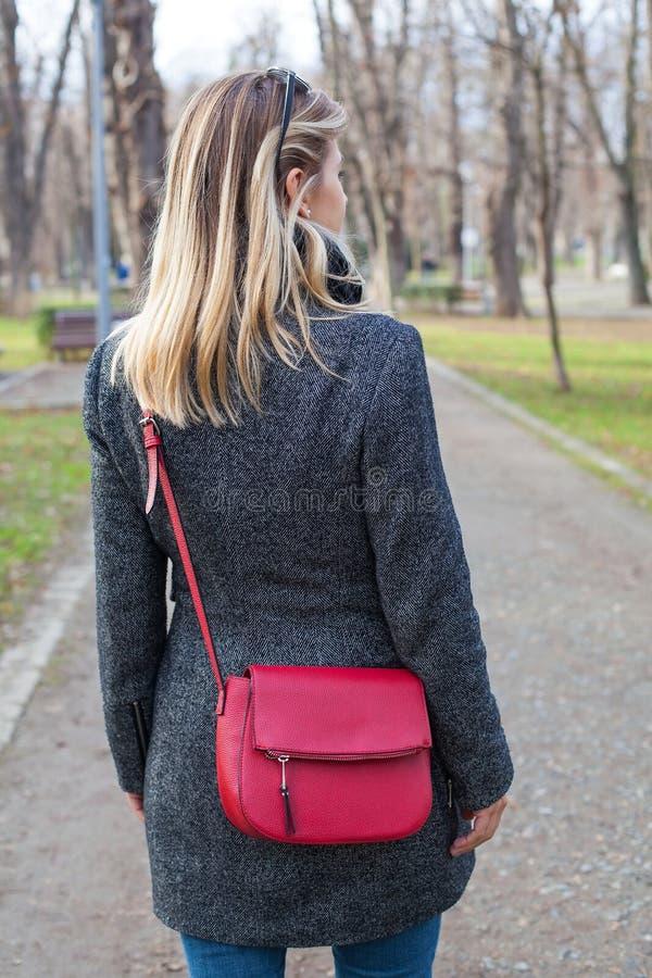 Mulher loura da vista traseira com o saco vermelho exterior fotografia de stock royalty free