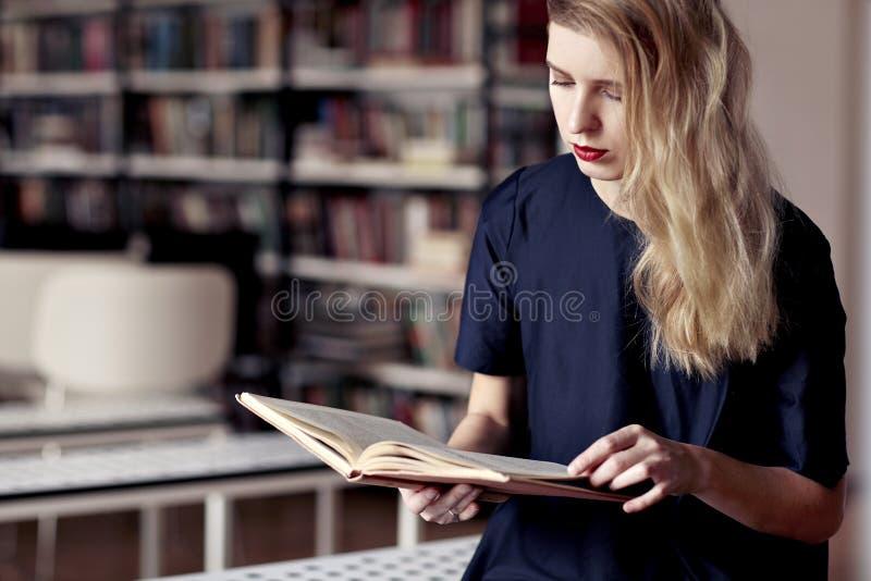 Mulher loura de Causasian que lê um livro em uma biblioteca pública Bordos vermelhos, cabelo branco longo fotos de stock