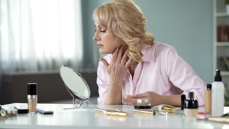 Mulher loura de meia idade que aplica a composição cara em casa, cosméticos antienvelhecimento fotografia de stock royalty free