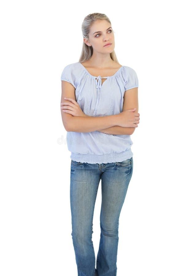 Mulher loura de pensamento que cruza seus braços foto de stock