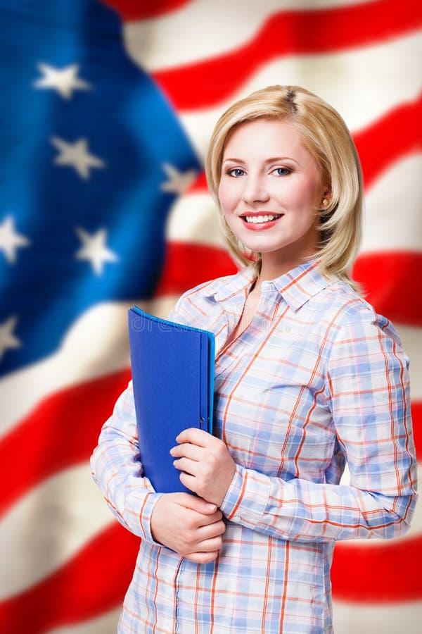 Mulher loura de sorriso atrativa na frente da bandeira dos EUA fotos de stock royalty free