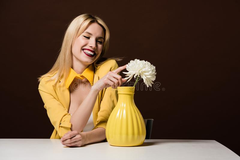 mulher loura de sorriso bonita no equipamento amarelo à moda que toca na flor branca no vaso foto de stock