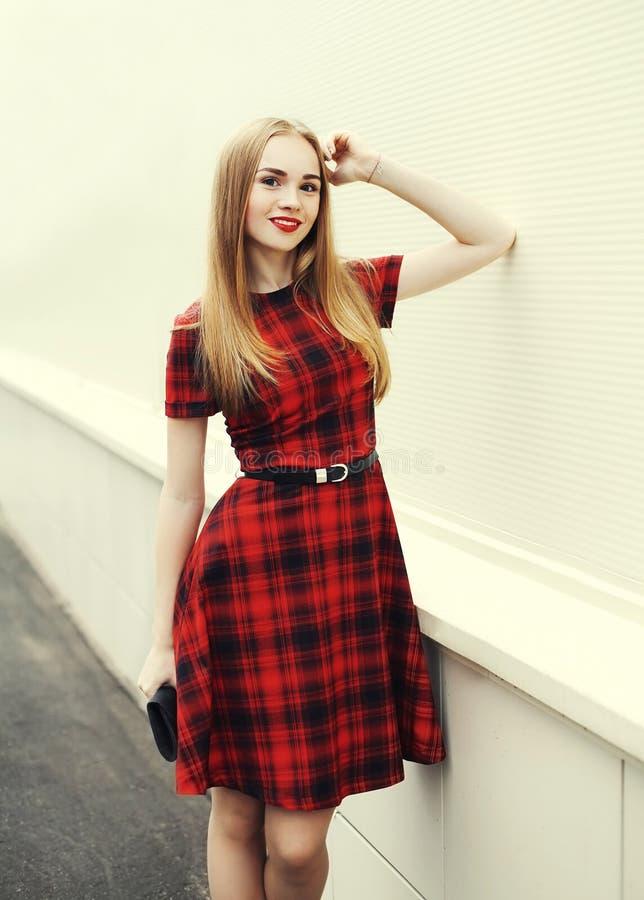 Mulher loura de sorriso bonita que veste o vestido quadriculado vermelho imagens de stock royalty free
