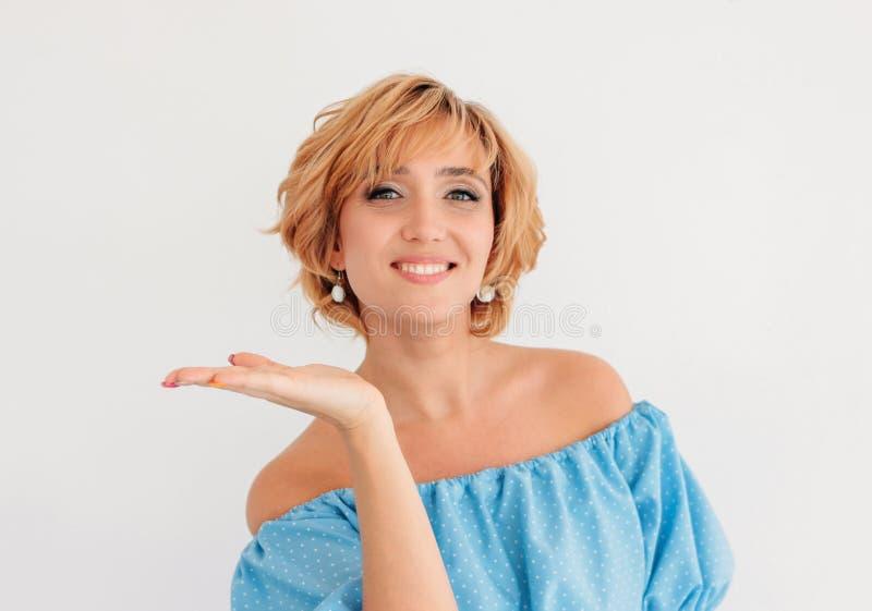 Mulher loura de sorriso encantador nova do cabelo curto no vestido azul do verão que faz o beijo do ar, isolado no fundo branco fotos de stock