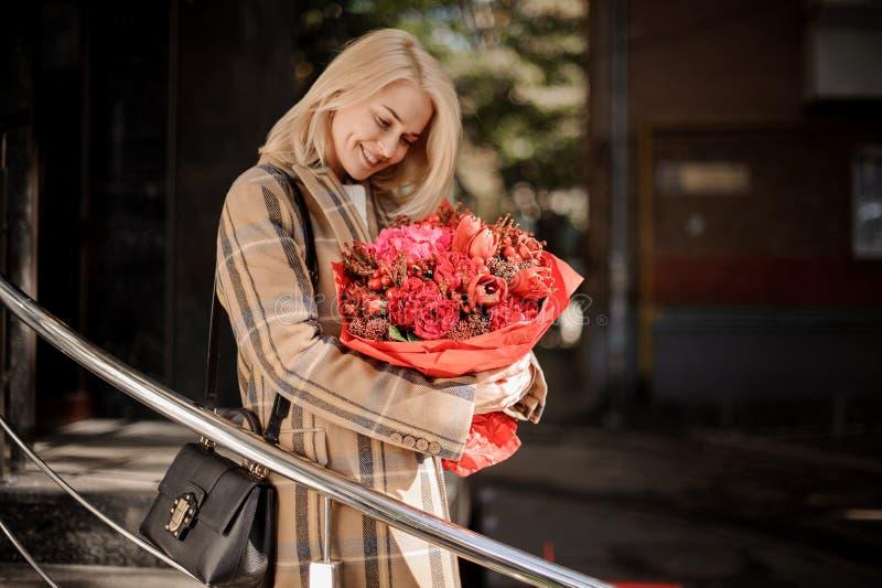 Mulher loura de sorriso feliz no revestimento da manta com um ramalhete vermelho grande fotos de stock royalty free