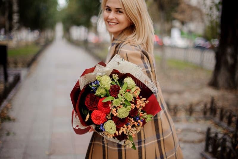 Mulher loura de sorriso feliz no revestimento da manta que guarda um bouque brilhante imagens de stock royalty free