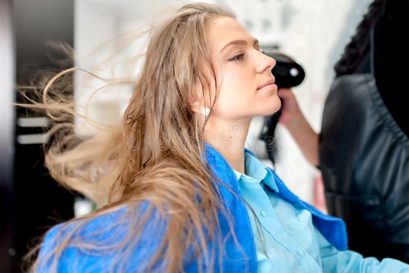 Mulher loura de sorriso no bar do cabelo usando um secador de cabelo imagem de stock royalty free