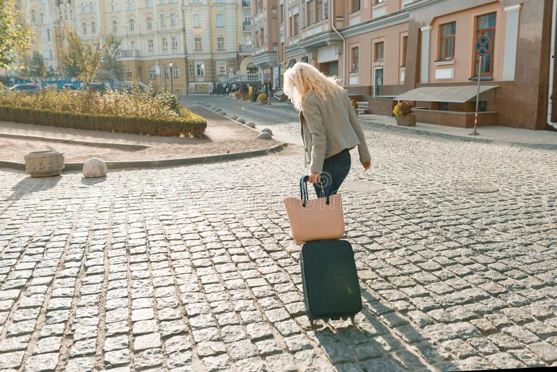 Mulher loura de sorriso nova com saco do curso e telefone que andam na rua da cidade, fêmea com cabelo encaracolado longo, vista  fotografia de stock royalty free