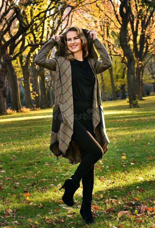 Mulher loura de sorriso nova no revestimento elegante que levanta consideravelmente no parque do outono imagem de stock royalty free