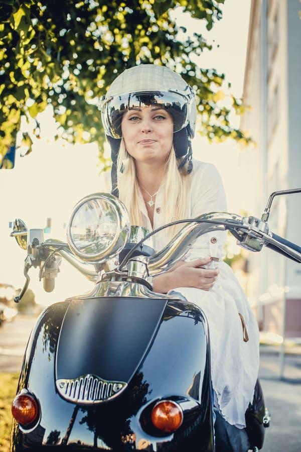 Mulher loura de sorriso ocasional no capacete do moto imagem de stock royalty free