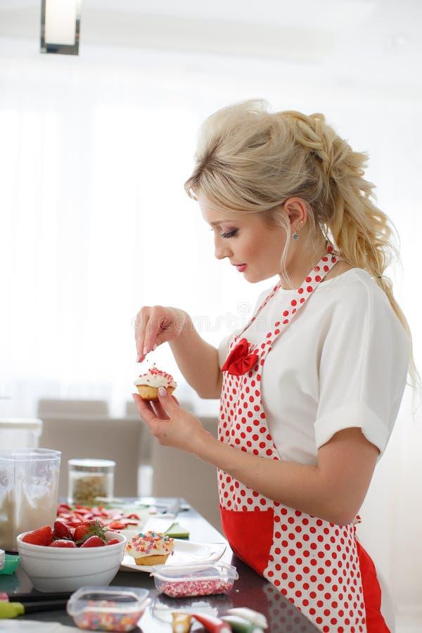 Mulher loura de sorriso que cozinha queques na cozinha fotografia de stock royalty free
