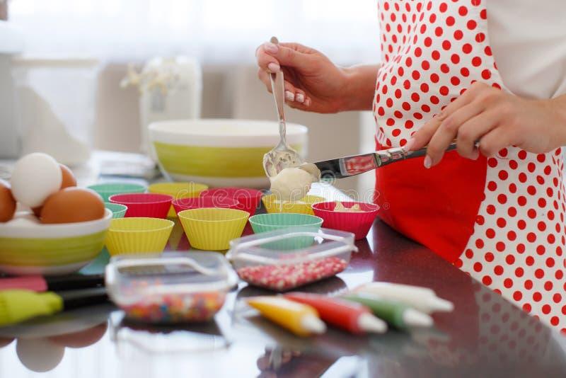 Mulher loura de sorriso que cozinha queques na cozinha foto de stock