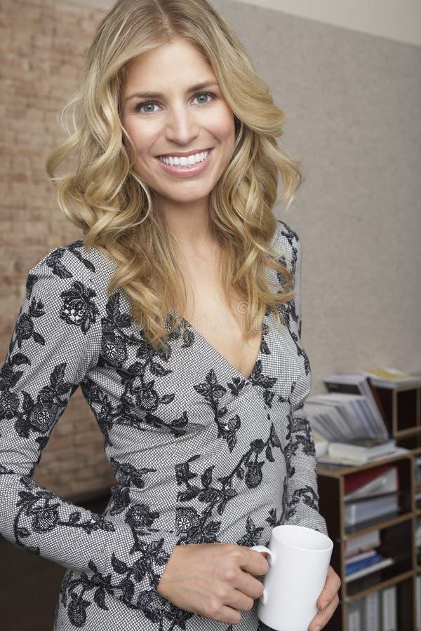 Mulher loura de sorriso que guarda a caneca no escritório imagem de stock