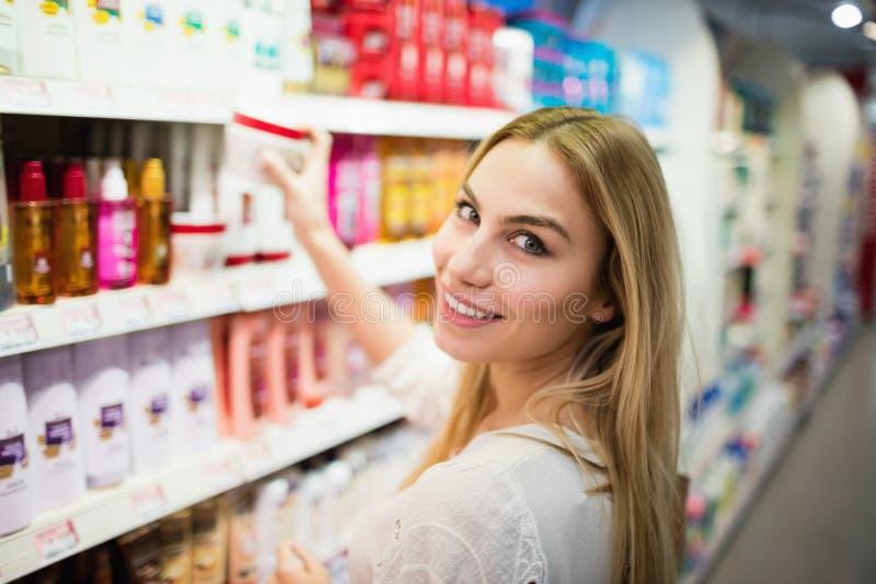 Mulher loura de sorriso que levanta ao escolher um produto imagem de stock royalty free
