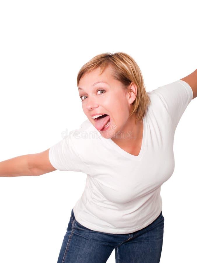 Mulher loura de sorriso que põr para fora sua lingüeta sobre o wh imagens de stock royalty free