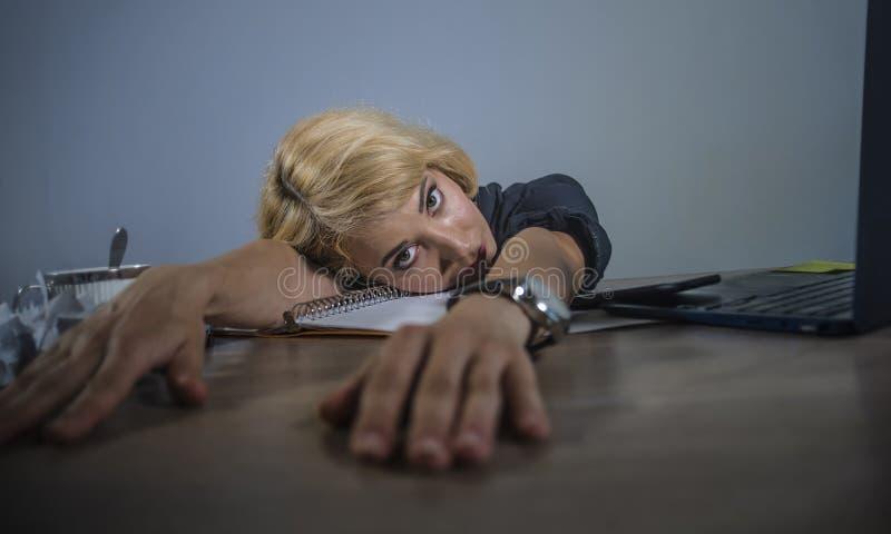 A mulher loura deprimida e triste bonita nova que trabalha com o laptop que sente a inclinação cansado baixo na mesa de escritóri imagens de stock royalty free