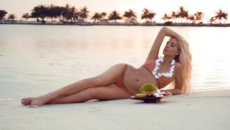 Mulher loura despreocupada que encontra-se na areia branca que aprecia o por do sol bonito na praia tropical Modelo 'sexy' do biq foto de stock