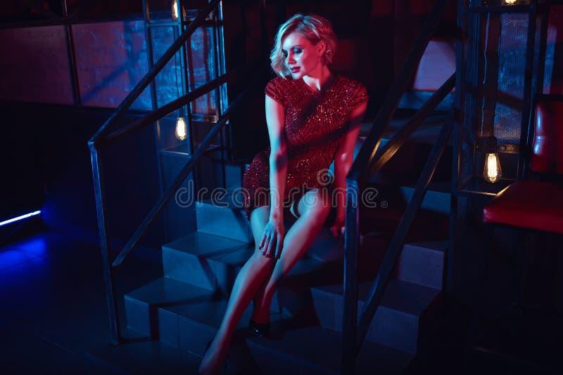 A mulher loura do encanto bonito com provocante compõe o vestido cabido curto vermelho vestindo da lantejoula que senta-se nas es fotografia de stock