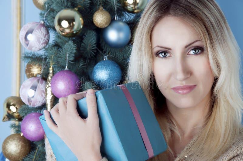 Mulher loura do Natal com um presente fotos de stock royalty free