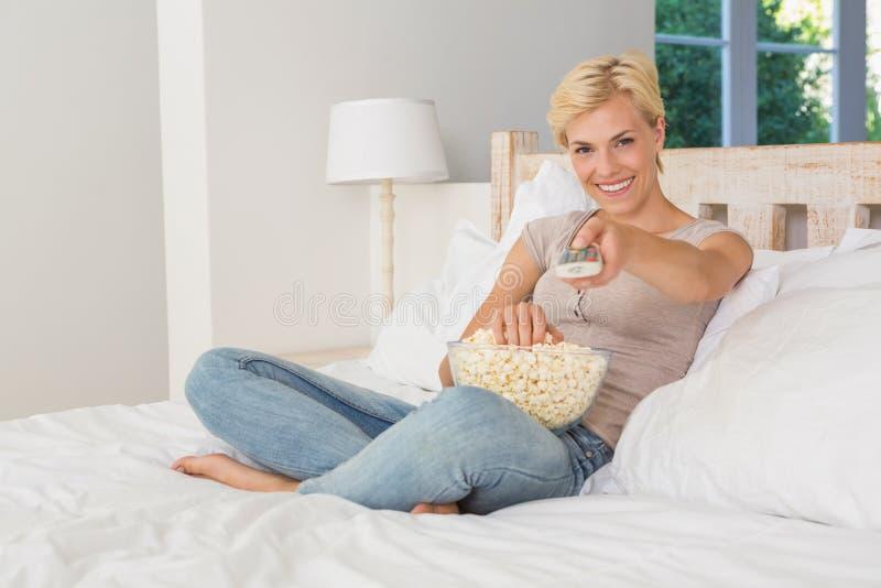 Mulher loura do retrato que watiching a tevê e que come o milho de PNF fotos de stock