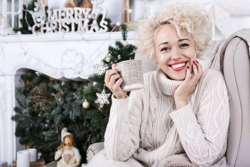 Mulher loura do sorriso grande bonito que senta-se no conforto acolhedor da cadeira home imagens de stock