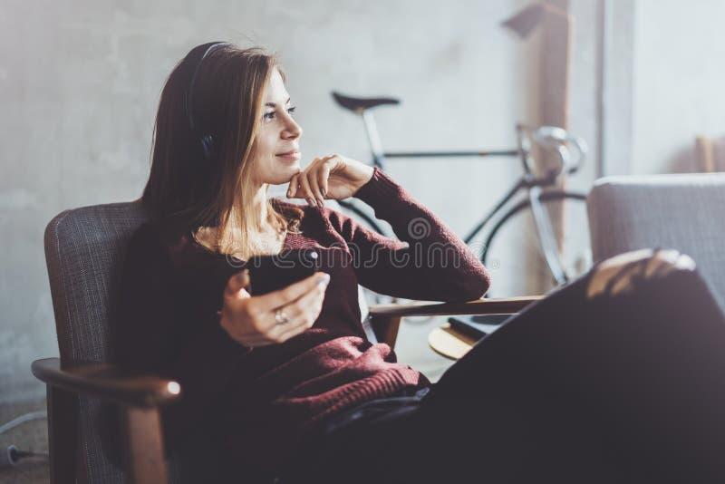 Mulher loura do yound que guarda o telefone celular moderno nas mãos Menina que aponta os dedos na tela móvel do toque vazio em e imagens de stock