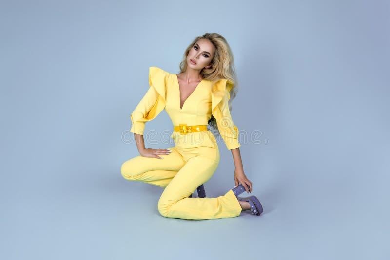 Mulher loura elegante no fato-macaco amarelo à moda e em acessórios elegantes no fundo da cor Modelo de forma bonito no azul imagem de stock royalty free
