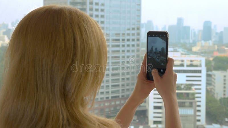 Mulher loura elegante que faz uma foto no telefone fotografias da mulher a vista da janela dos arranha-céus imagens de stock