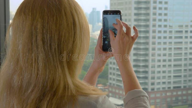 Mulher loura elegante que faz uma foto no telefone fotografias da mulher a vista da janela dos arranha-céus foto de stock royalty free