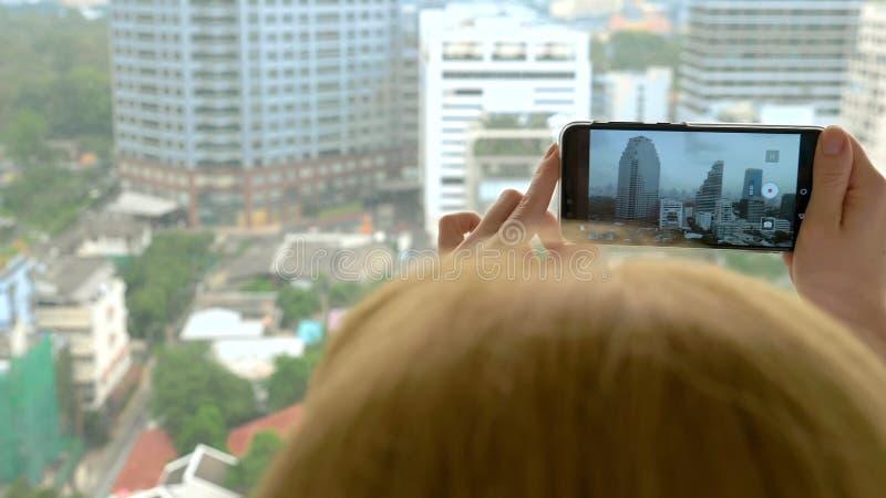 Mulher loura elegante que faz uma foto no telefone fotografias da mulher a vista da janela dos arranha-céus fotografia de stock royalty free