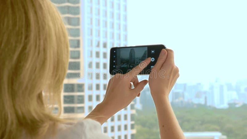 Mulher loura elegante que faz uma foto no telefone fotografias da mulher a vista da janela dos arranha-céus imagem de stock