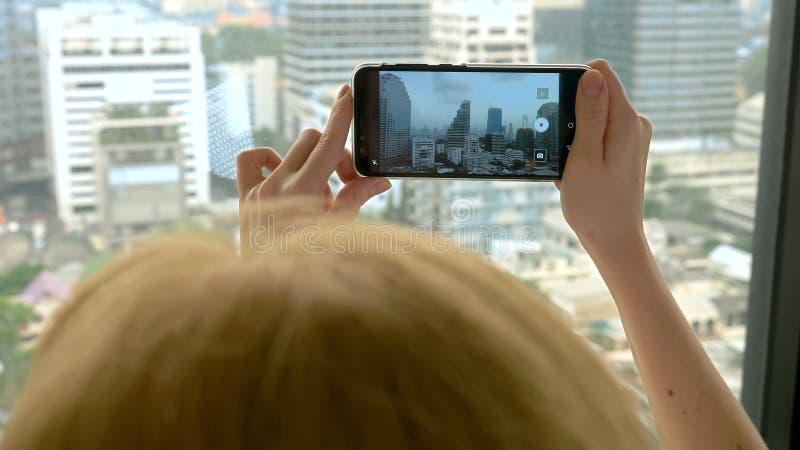Mulher loura elegante que faz uma foto no telefone fotografias da mulher a vista da janela dos arranha-céus imagens de stock royalty free