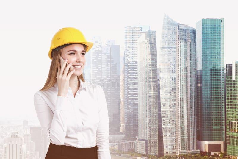 Mulher loura em um capacete de segurança em uma cidade imagens de stock