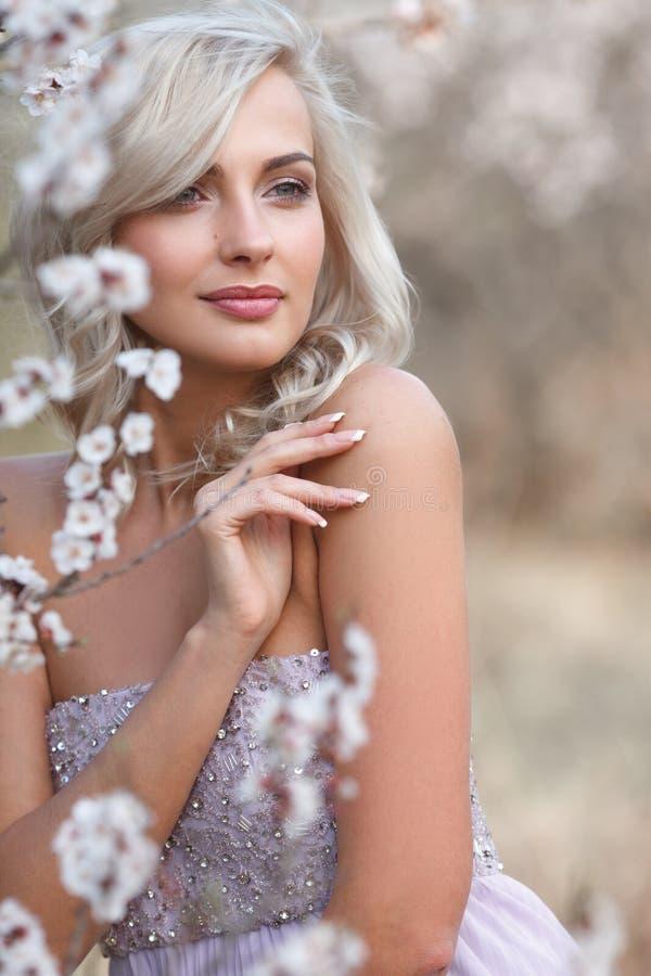 Mulher loura em um jardim florescido fotografia de stock royalty free