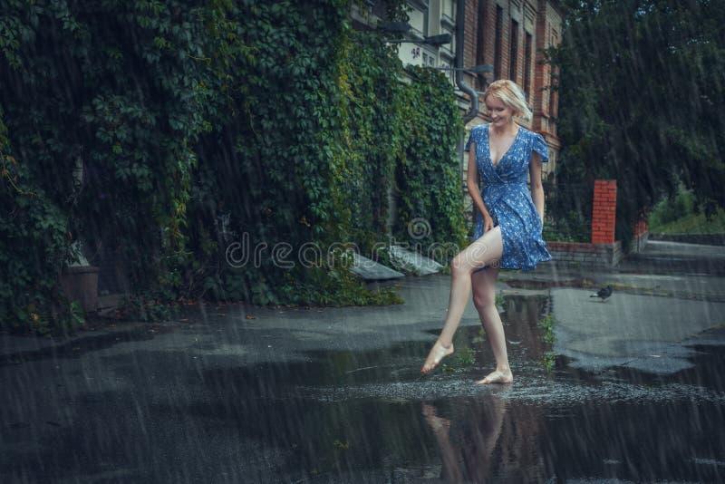 A mulher loura em um vestido faz correria na chuva do verão foto de stock